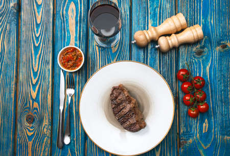 Grilled beef steak, salt and pepper and wine on wooden table. Top view with copy space