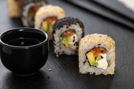 Sushi roll with rice, cucumber, avocado, salmon, sesame. Sushi menu. Japanese food. Standard-Bild