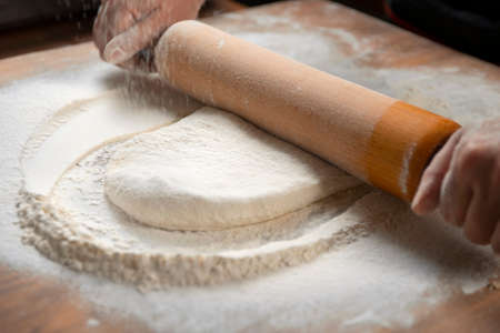 Baker kneading dough for pizza preparation. Chef cook making dough for baking pie on wooden table. Process preparation homemade pastry. Cooking pasta, bread, spaghetti, khachapuri, food concept