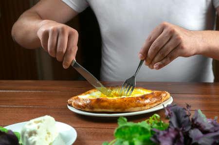 Man eating adjar Khachapuri. Georgian national pie khachapuri with egg and cheese in the white plate on wooden background. Archivio Fotografico