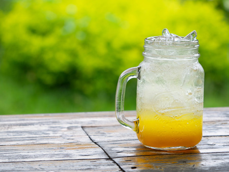 A fresh orange soda drink filled with ice in a vintage style glass container Full of ice in the glass. Placed on a wooden desk in garden with a green background Stok Fotoğraf