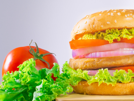 The hamburgers with meat and vegetables putting in layer. It is the food of the Westerners. Moreover, It is the easy food concept in every area.