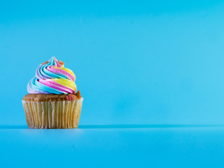 Colorful and enteresting cupcake isolated on blue background studio close up shot.