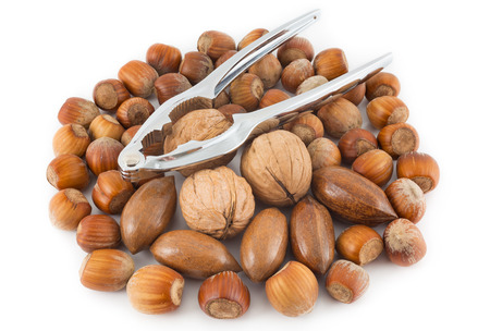 Mixed nuts and nutcracker on a white background photo