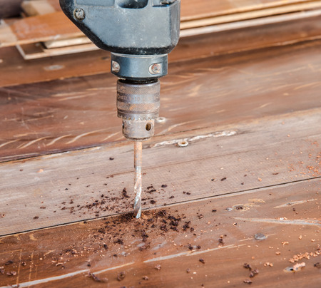 hand drill: Electric hand drill drilling wood board Stock Photo