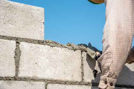 Worker making concrete wall by plaster and cement block at construction site Stock Photo