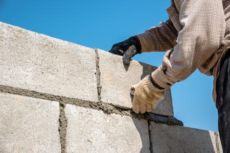 De arbeider die van betonnen muur van gips en cement blok op bouwplaats