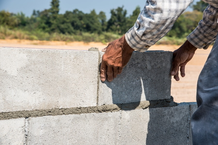 stone mason: Worker making concrete wall by plaster and cement block at construction site Stock Photo