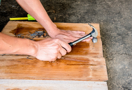 nailing: Carpenter nailing by hammer when making furniture from wood board
