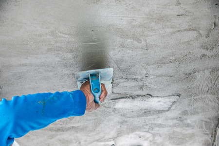 plastering: worker plastering the ceiling and wall concrete