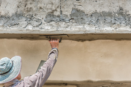 stone mason: worker plasterize the ceiling and wall concrete Stock Photo