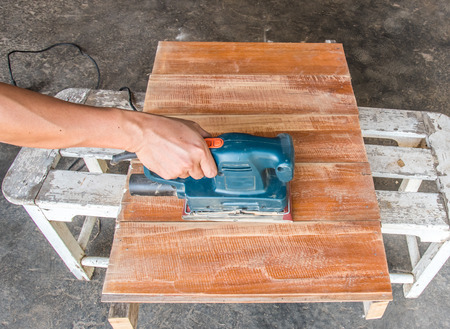 sander: carpenter use electric sander polish wood board