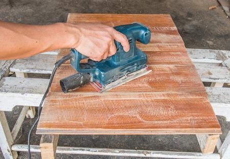 sander: carpenter use electric sander polish wood board