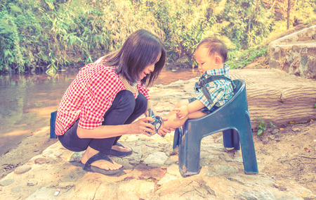 sitter: Mother wearing shoe to baby at outdoor park Stock Photo