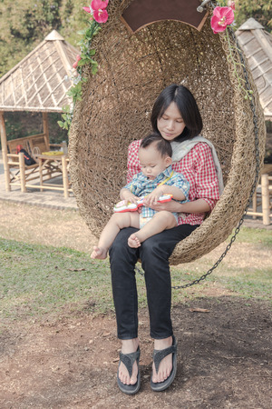 young mother holding baby on rattan swing. Byby play guitar toy in the mother hug photo