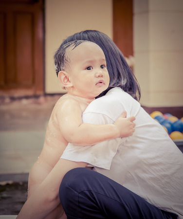 soothe: Asian mother soothe baby to stop crying Mother hug baby infront of huosemother protect baby from scarrying