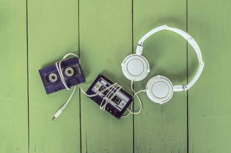 Cassette tape and head phone on green color wood board photo