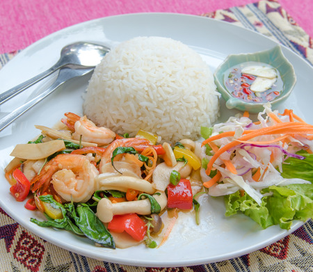 Stir-fried shrimp with holy basil and rice set serve with fish sauce mixed with red chili and lime . (Thai food name is PAD KRAPAO ) photo