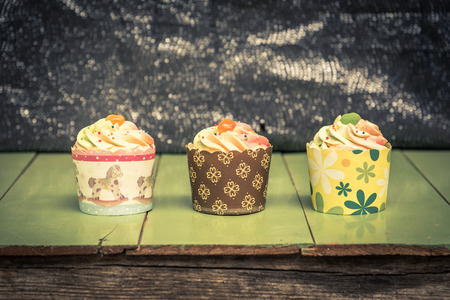 tree cup cake put on the green wood board with bokeh backdrop , vintage color tone effect photo