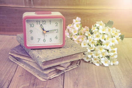 corner clock: Alarm clock and old diary book put on the wood floor together with flower . effected by ray of light from top right corner.