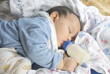 Asian baby sleeping and drinking milk from the bottle Stock Photo