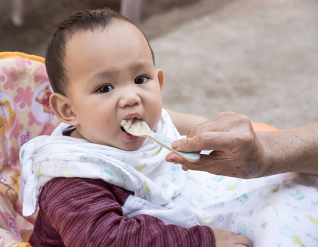 grand sons: Baby eating food by mother feeding, family scene of Thailand