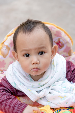 grand kids: Portrait baby with food stick on cheek and mouth after eating Stock Photo