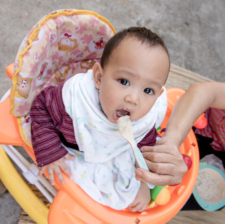 grand kid: Baby eating food by mother feeding, family scene of Thailand