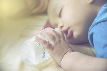 teteros: primer plano la mano del bebé y el dedo. Bebé que sostiene la botella mientras se duerme Foto de archivo