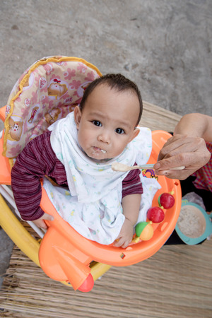 grand son: Baby eating food by mother feeding, family scene of Thailand