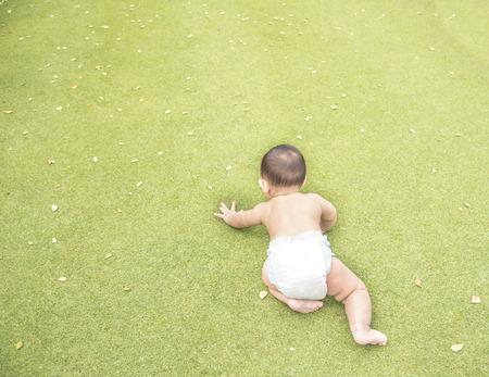 bebe sentado: Adorable Bebé asiático que se arrastra en el campo de hierba verde cuando se juega en el parque. Foto de archivo