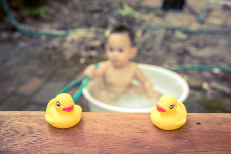 yellow duck: yellow duck on wood board  with blurred  baby bathing background