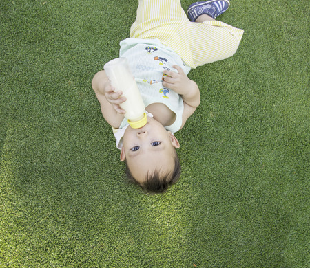 Adorable Asian baby boy laying on the grass field and  drinking milk from bottle when picnic with family in the out door park, up side down photo