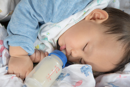 New born baby sleeping while drinking mother milk from  bottle Stock Photo