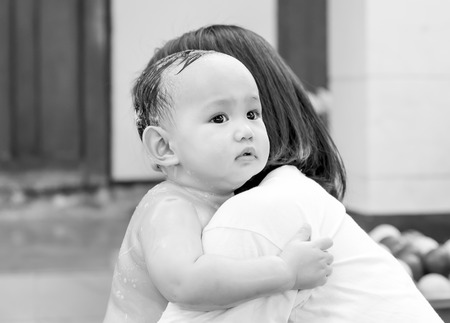 fear child: Fear , Asian baby in motion of fearing . His hand holding mother tightly in the mother hug.