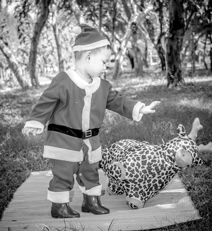 santaclaus: A kid in Santaclaus suit push reindeer doll away , unfriend concept  and black and white photography with vignette Stock Photo
