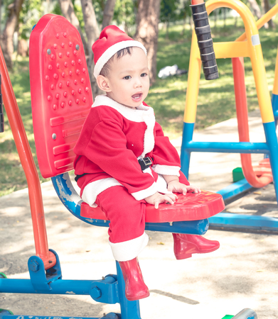 baby in suit: Asian baby boy in santa claus suit is playing with reindeer doll at outdoor park Stock Photo