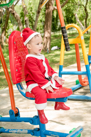 baby in suit: Asian baby boy in santa claus suit is playing  at the outdoor park