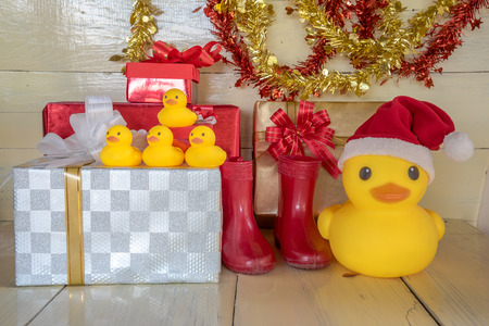 santa clause hat: Christmas concept, rubber yellow duck, Santa clause hat  and gift boxes set as Christmas decoration on white color wood board. Stock Photo