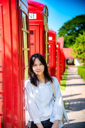 cabina telefonica: retrato de la se�ora asi�tica que se coloca al lado de la cabina de tel�fono roja