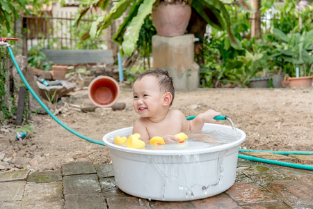 yellow duck: Asian baby boy outdoor bathing in the white bathtub . He is smiling and playing yellow duck full of happiness, Country side culture of Thailand