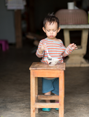 baby rice: Asian baby boy eating rice by spoon by him self
