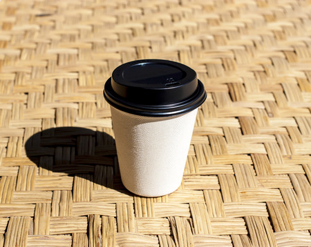 rattan mat: paper coffee cup put on rattan mat against the morning light with black shadow Stock Photo
