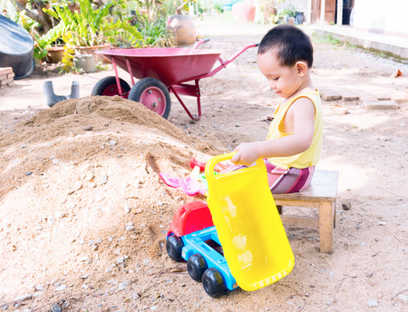 fork spoon: Thai baby boy palying on  pile of sand with toy and plastic fork, spoon , truck ,wheel barrow Stock Photo