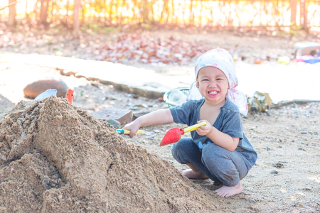 fork spoon: Thai baby boy palying on  pile of sand with toy and plastic fork, spoon
