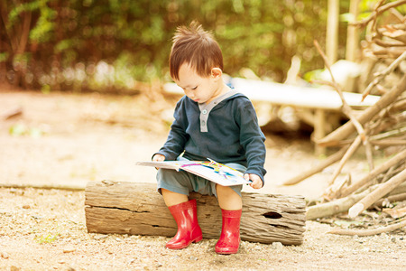 Asian baby boy  reading tale book , Boy wear red boot sitting on a log . Stock Photo