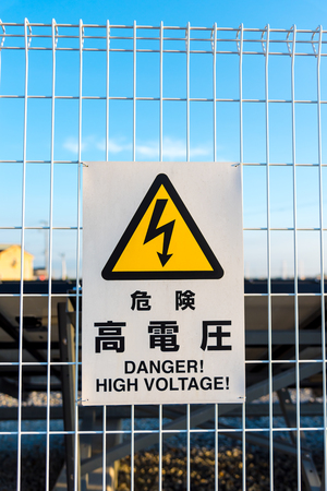 volts: warning signs of high voltage in Japanese and English language  attach on white fence Stock Photo