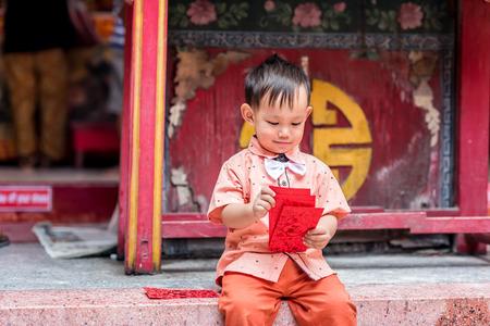 Bebé asiático asimiento sobre rojo o Ang-pow. El niño sonriente porque se siente la felicidad de un regalo de año nuevo chino. Foto de archivo - 65734718