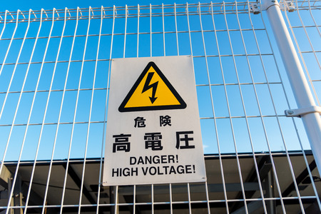 warning signs of high voltage in Japanese and English language  attach on white fence 写真素材