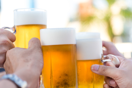 Hand holding glasses of beer  clinking together at outdoor resturant